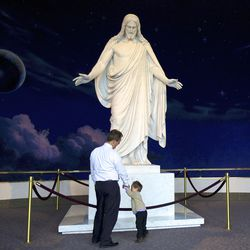 Joao Oliveira and his son Thomas, both of Brazil stand in front of the Christus statue on Temple Square during the morning session of the 180th Annual General Conference of The Church of Jesus Christ of Latter-day Saints in the Conference Center in Salt Lake City, Saturday, April 3, 2010.