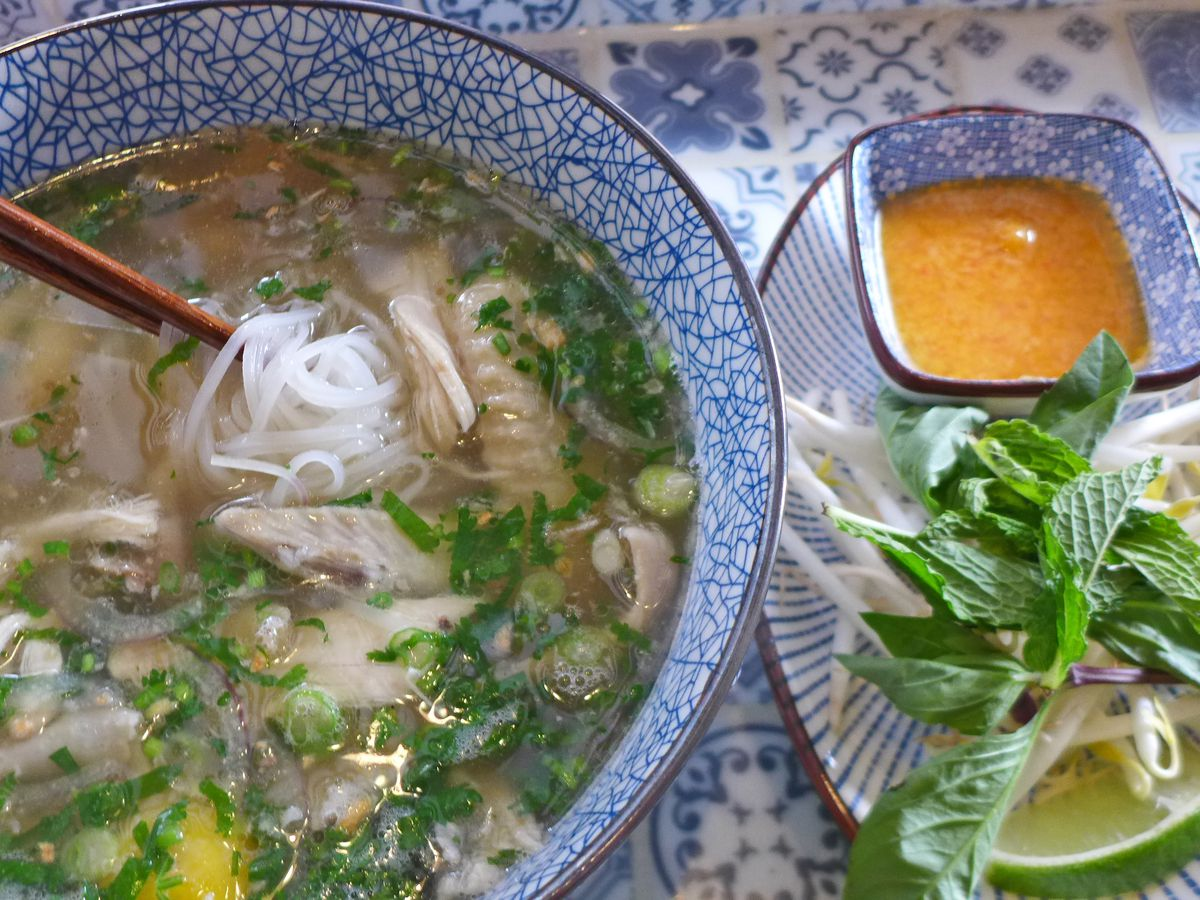 A soup with chicken parts and white noodles visible, with herbs and an orange dipping sauce, all on a filigreed blue background.