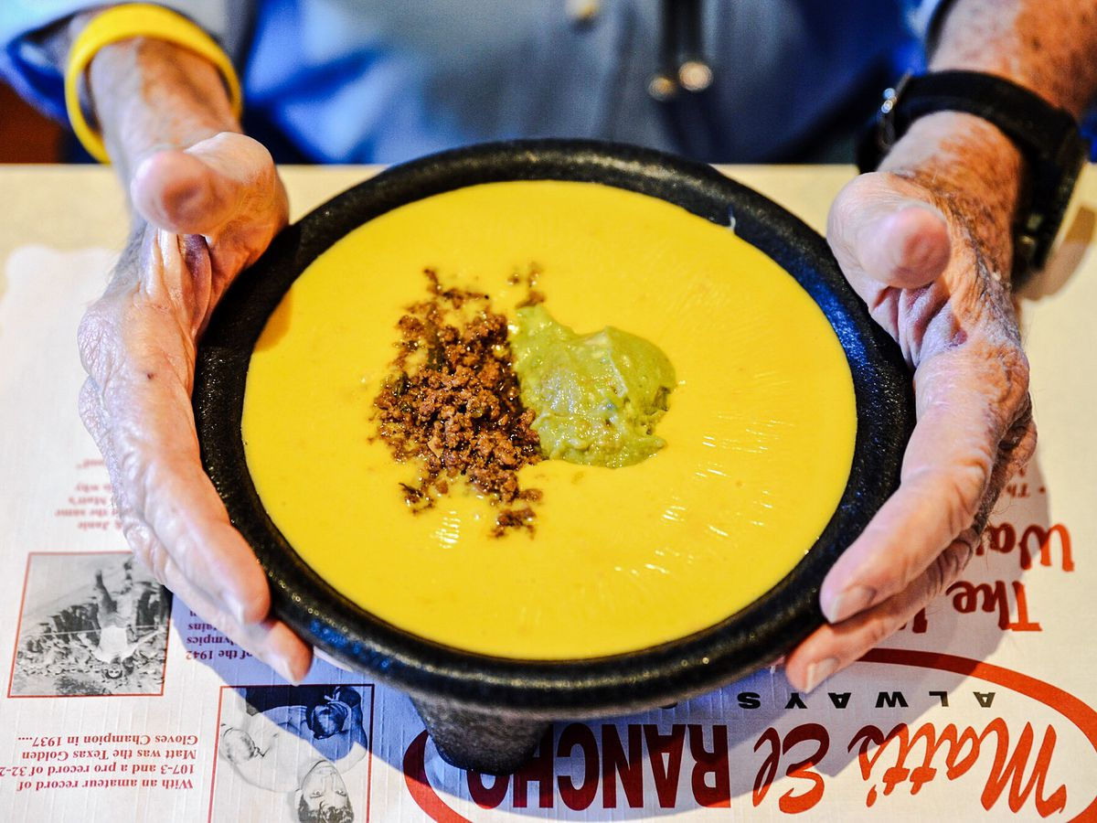 A pair of hands holding onto a bowl of yellow cheese dip with dollops of ground meat and guacamole on top of a placemat that notes information about Matt's El Rancho