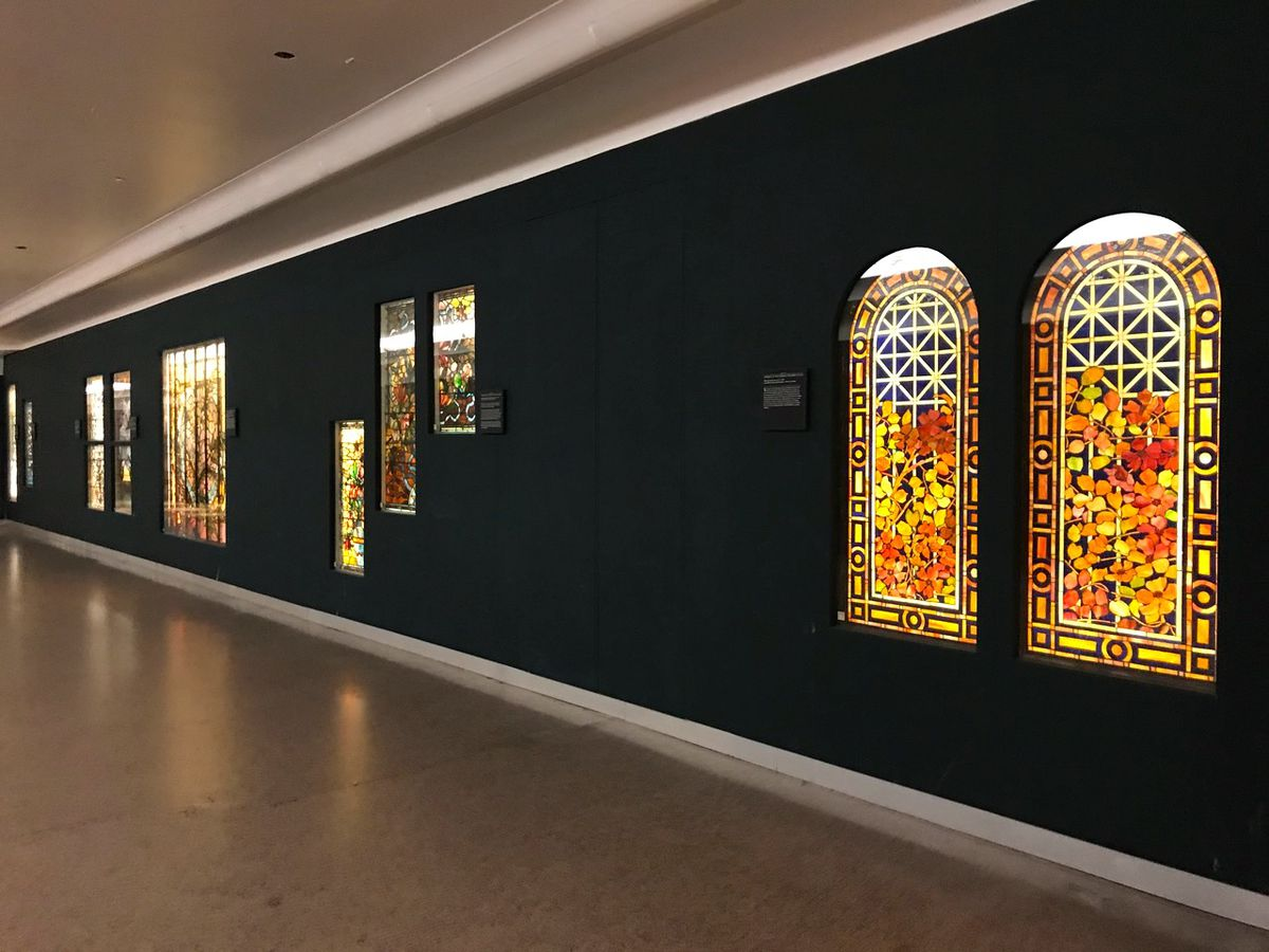 A hallway with a black wall and two arched stained glass windows, with more in the distance. They are back light with flowery and traditional designs.