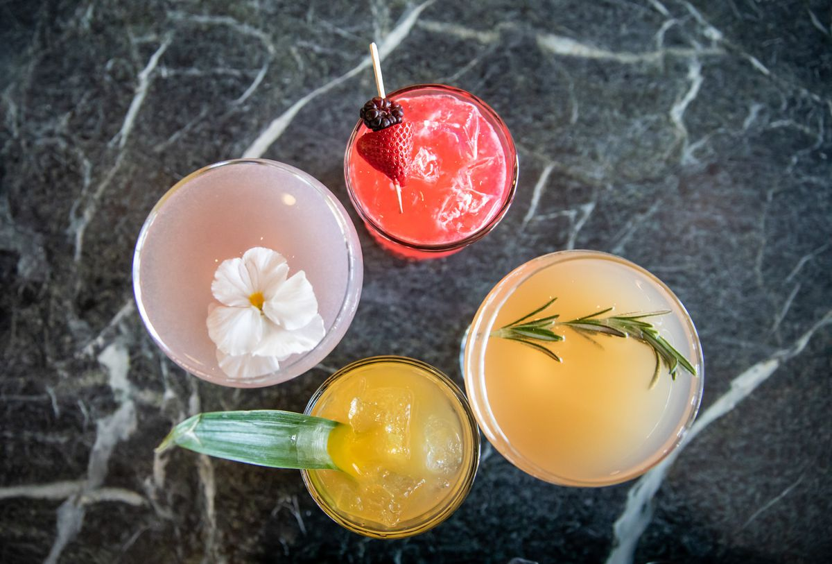 four colorful cocktails with sprigs of rosemary, berries, and edible flowers