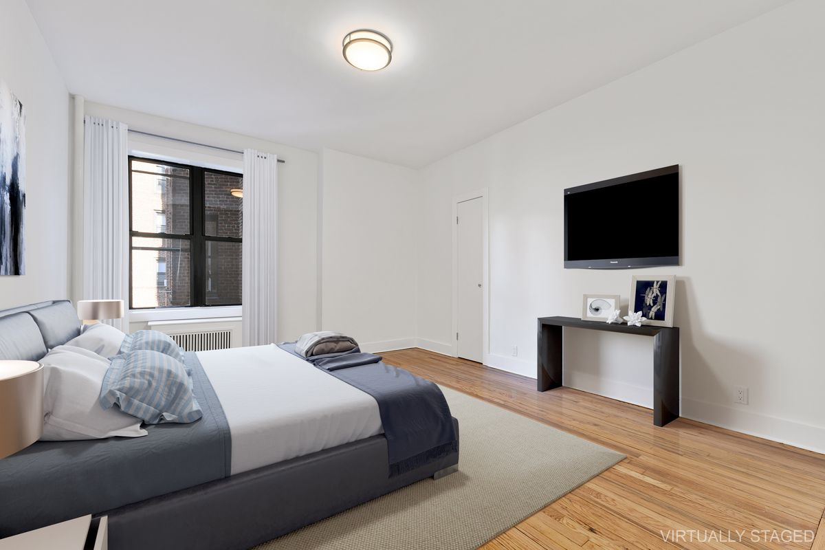 A large bedroom with a bed, base moldings, and hardwood floors.