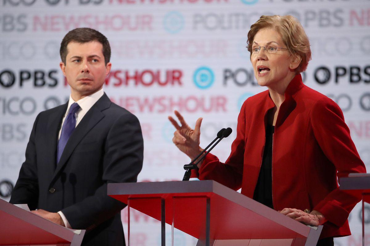Pete Buttigieg and Elizabeth Warren stand at podiums on a debate stage.
