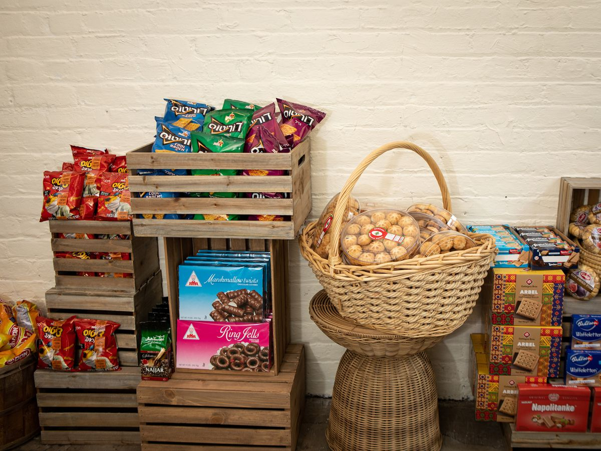 A selection of boxed Israeli snacks appear in baskets and boxes against a painted white brick wall