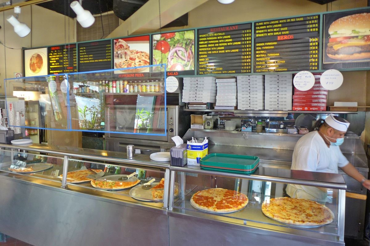 A long glass counter displaying pizzas while a man in a ponytail is seen at the right of the picture.