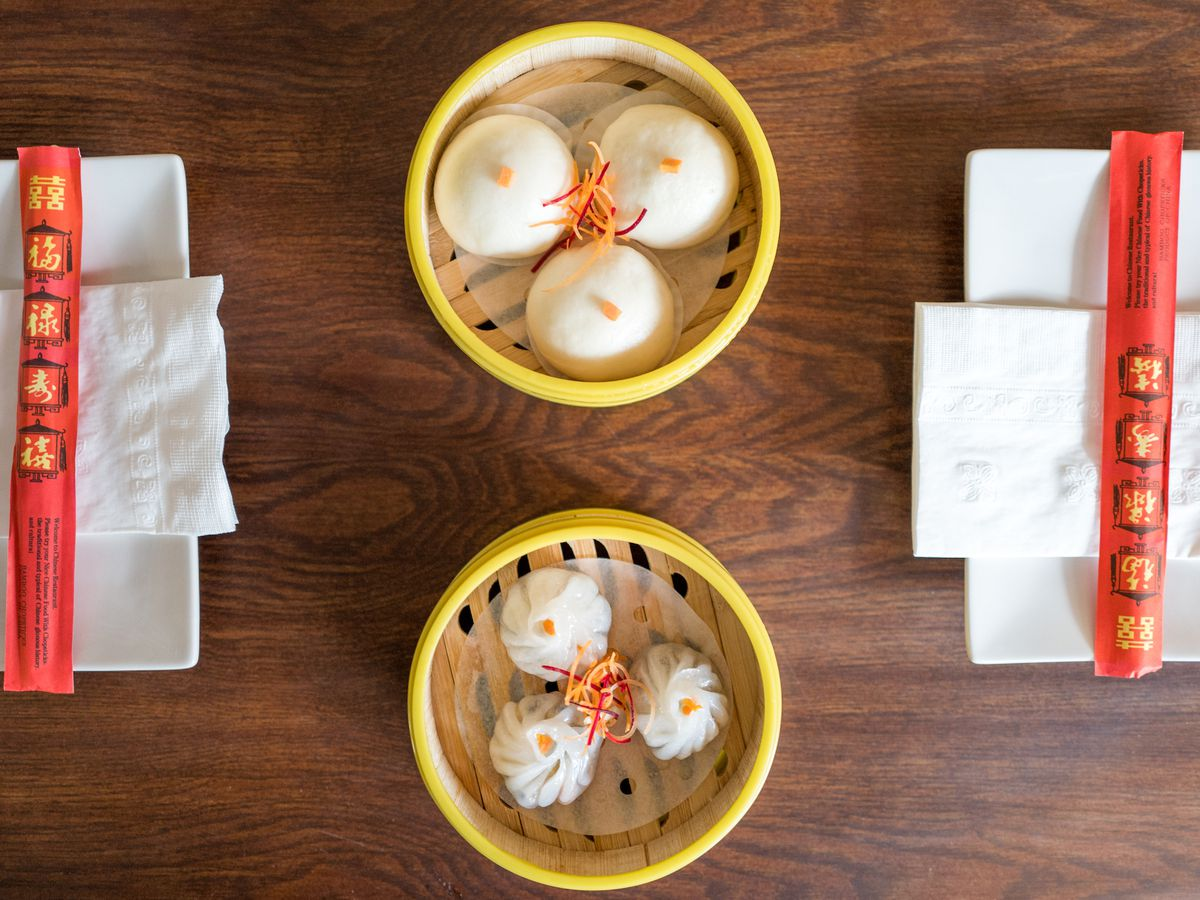 An aerial photograph of two wooden steamer baskets filled with dim sum dishes