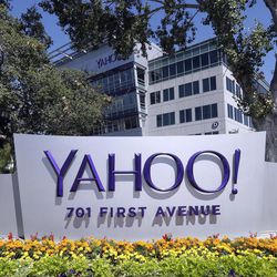 FILE - In this July 19, 2016, file photo, flowers bloom in front of a Yahoo sign at the company's headquarters in Sunnyvale, Calif. On Tuesday, June 13, 2017, Verizon took over Yahoo, completing a $4.5 billion deal that will usher in a new management team to attempt to wring more advertising revenue from one of the internet's best-known brands. Tuesday's closure of the sale ends Yahoo's 21-year history as a publicly traded company. It also ends the nearly five-year reign of Yahoo CEO Marissa Mayer, who isn't joining Verizon.