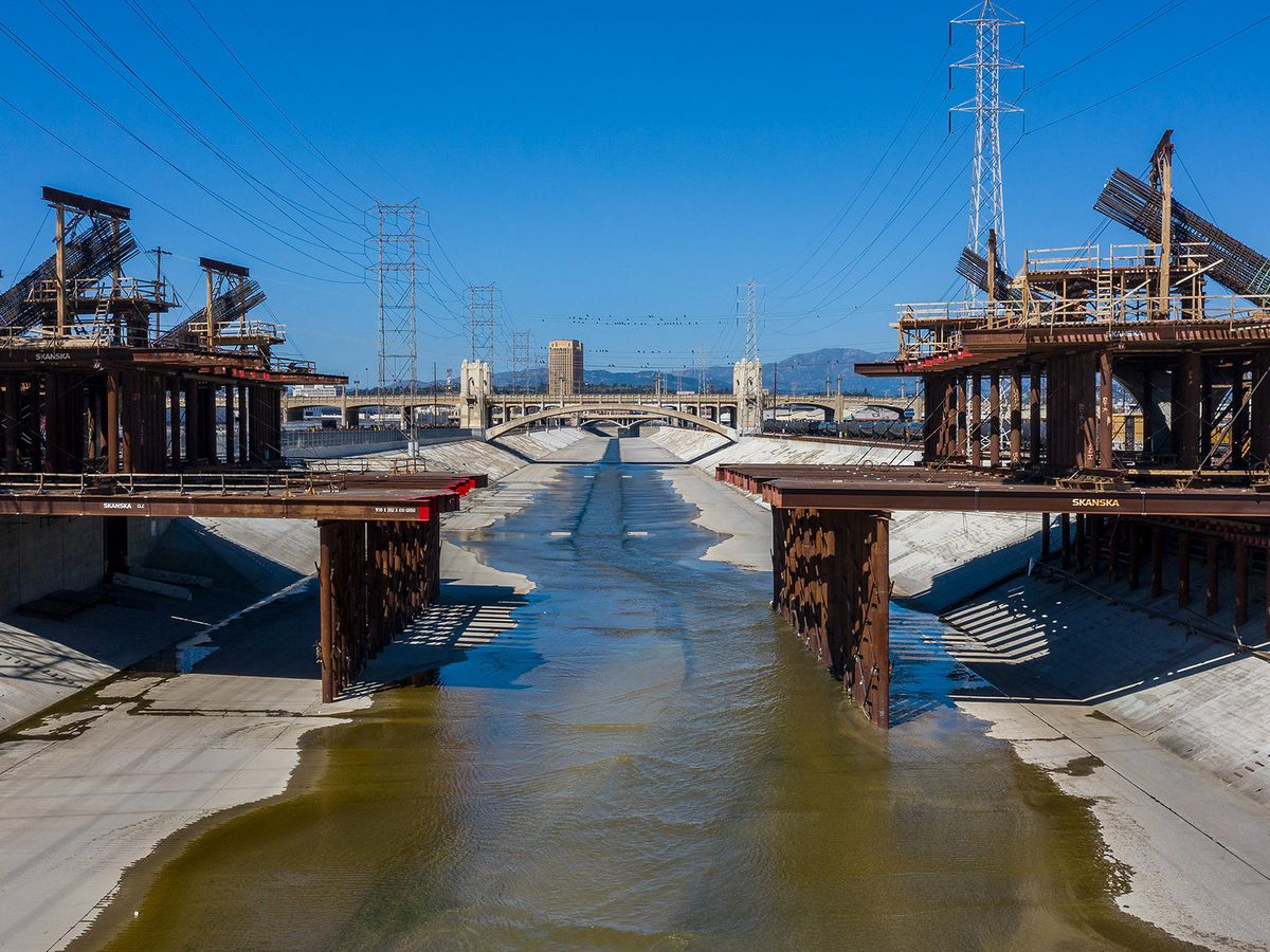 The exterior of the Sixth Street Viaduct in Los Angeles. There is a viaduct spanning over a shallow river bed.