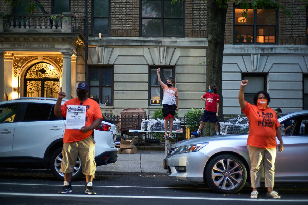 Residents on a diverse stretch of St. John's Place in Prospect Heights, Brooklyn show their solidarity with the Black Lives Matter movement during a socially-distanced block party, Aug. 8, 2020.