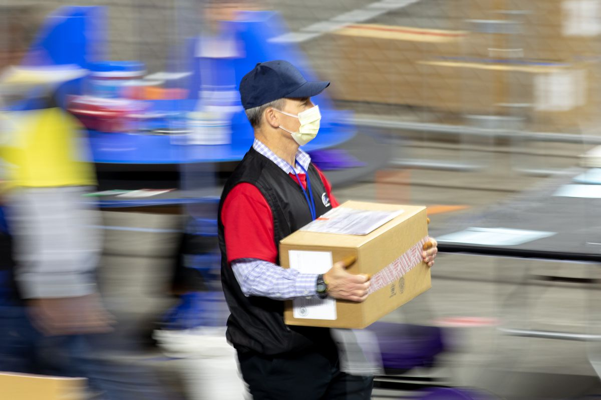 A person carrying a cardboard box. The background is blurred.