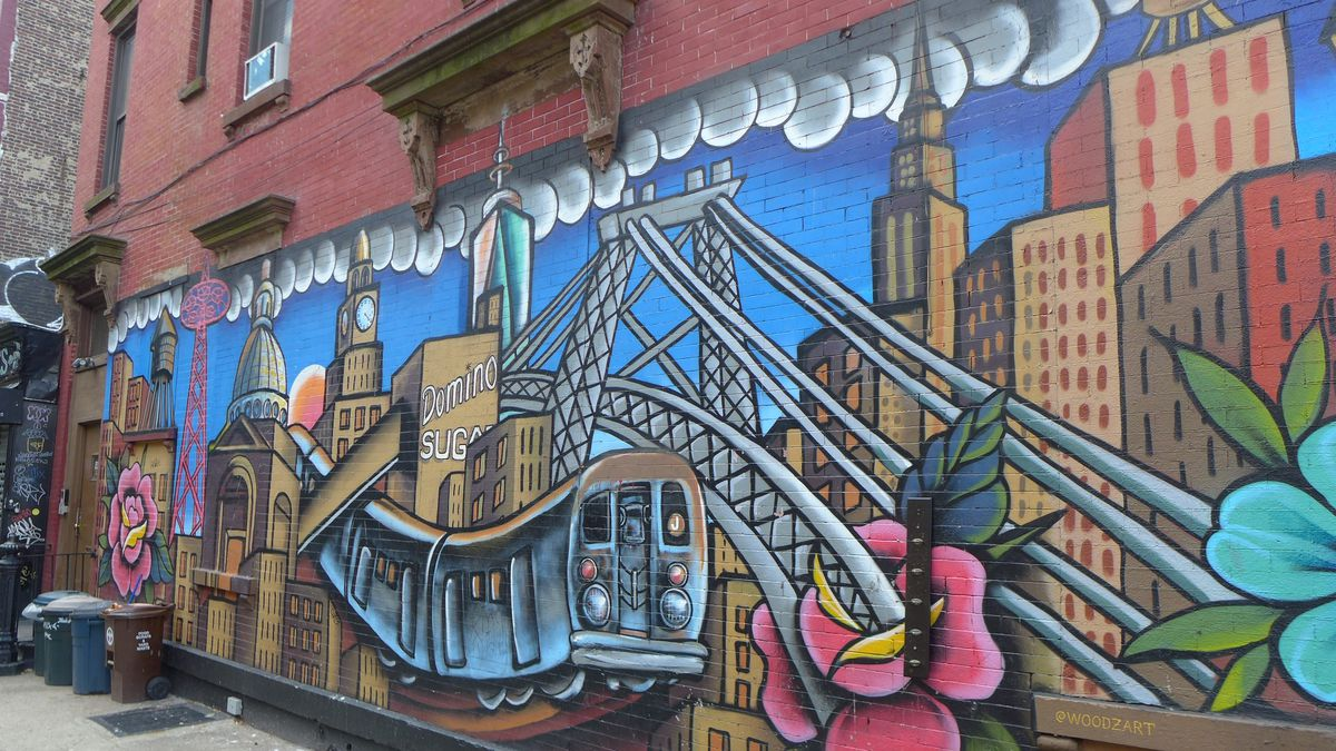A colorful mural showing the Williamsburg Bridge and other Williamsburg landmarks intertwined.