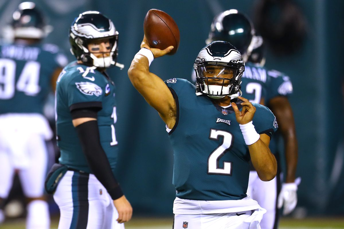 Jalen Hurts #2 warms up as Carson Wentz #11 of the Philadelphia Eagles looks on against the Seattle Seahawks at Lincoln Financial Field on November 30, 2020 in Philadelphia, Pennsylvania.