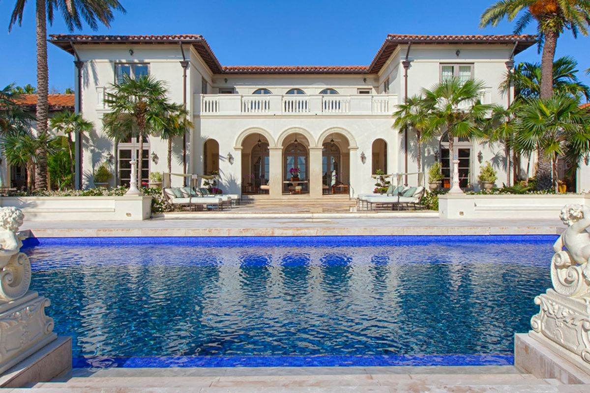 A waterfront mediterranean home in coral gables with two sculptures overlooking the resort-style pool