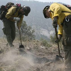 In this June 2, 2012 file photo, firefighters from the Granite Mountain Hotshots of Prescott, Ariz. cut a fire line along a mountain ridge in the Gila National Forest outside Mogollon, N.M. On Sunday, June 30, 2013, a fast-moving wildfire killed 19 firefighters from the Prescott-based group after the blaze raced through the central Arizona town of Yarnell, about 85 miles northwest of Phoenix. (AP Photo/U.S. Forest Service, Tara Ross)