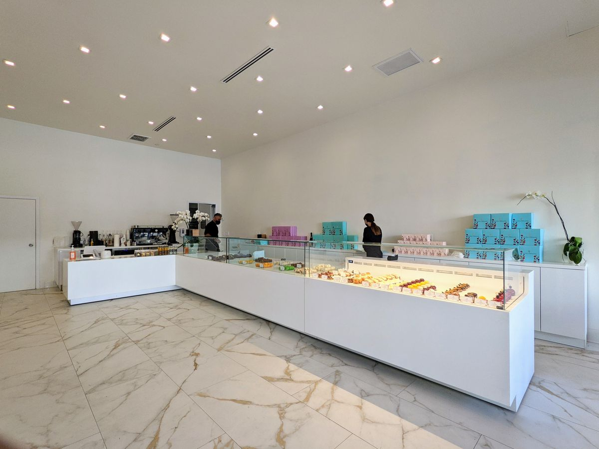 An L-shaped marble display case in a bare white room, showing French pastries.