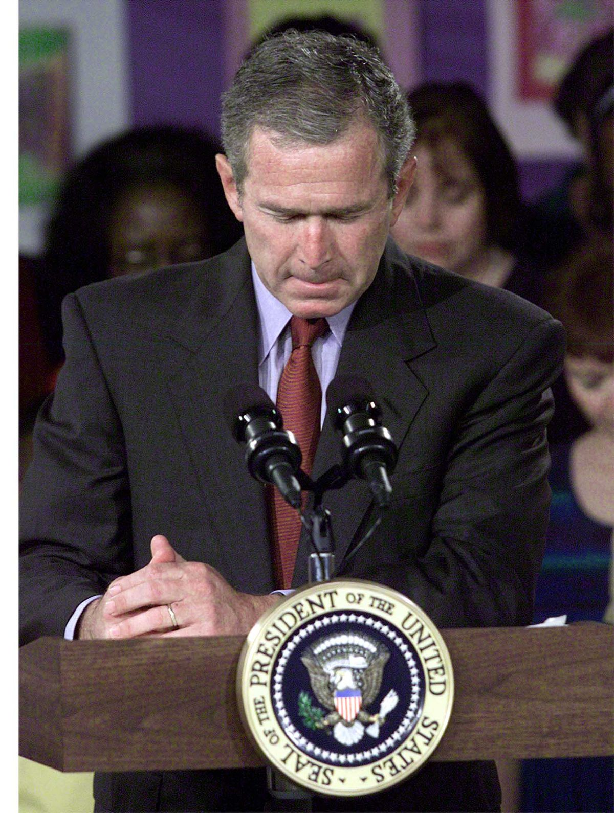 President Bush bows his head for a moment of silence following the plane crashes into the World Trade Center, during a visit to the Emma E. Booker Elementary School in Sarasota, Fla., Tuesday, Sept. 11, 2001.