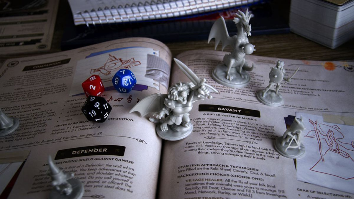 Dice and miniatures, including a plastic Manticore, stand on top of the Quest of Yore rulebook with a few dice.