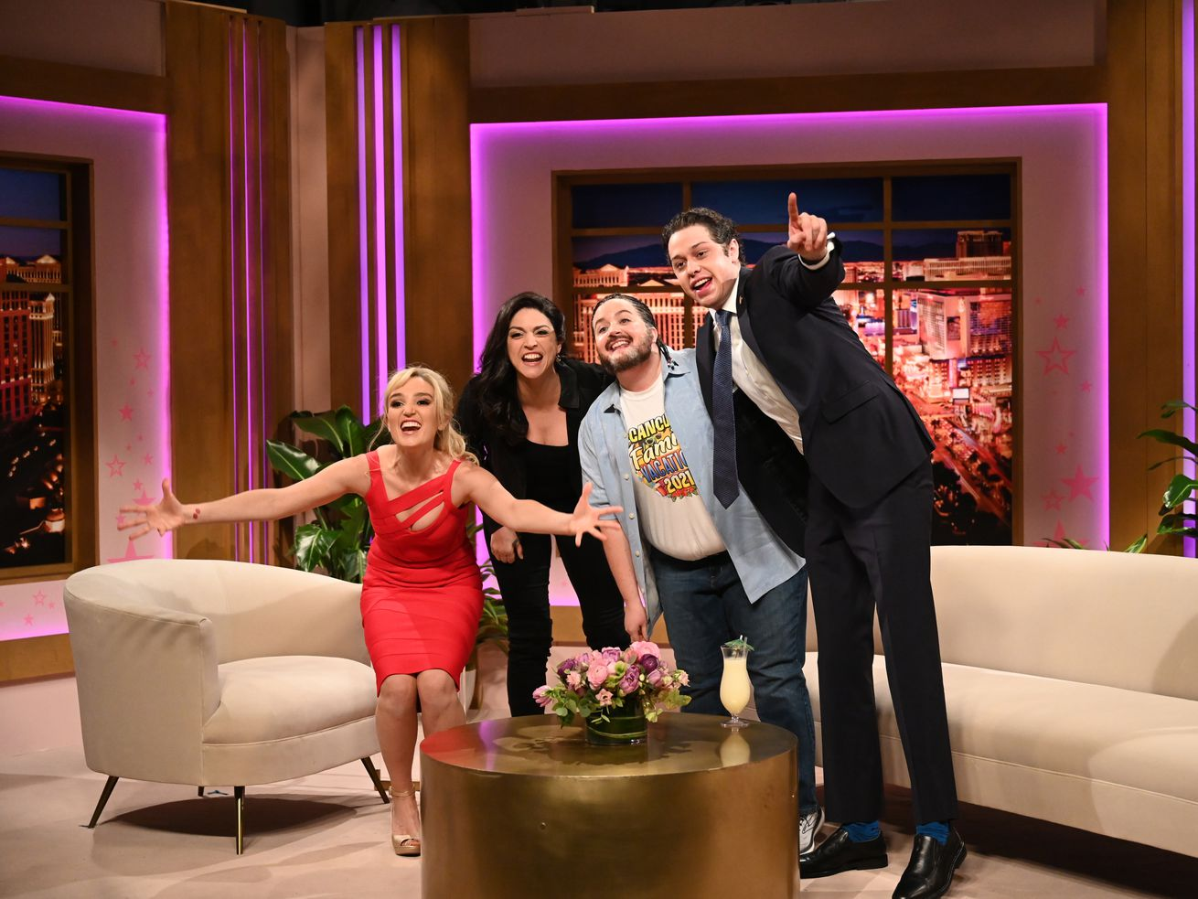"""Chloe Fineman as Britney Spears, Cecily Strong as Gina Carano, Aidy Bryant as Ted Cruz, and Pete Davidson as Andrew Cuomo huddle together in front of cream colored chairs on a talk show stage, shouting, """"Live from New York, it's Saturday Night Live!"""""""