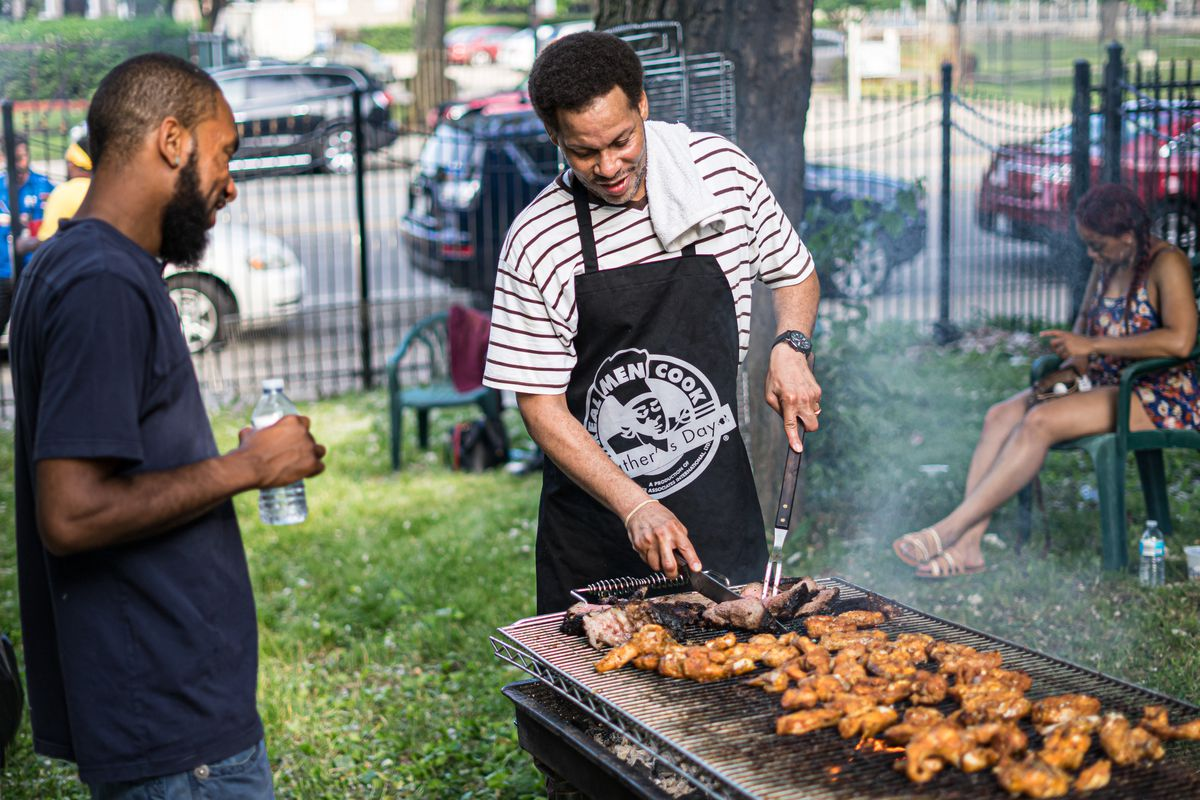 """Two men enjoy last year's """"Real Men Cook"""" festival. This year's takes place Sunday — Father's Day — at Hales Franciscan High School on the South Side."""