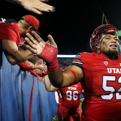 Utah Utes defensive tackle John Penisini (52) greets fans after his team's win over the Brigham Young Cougars at LaVell Edwards Stadium in Provo on Saturday, Sept. 9, 2017.