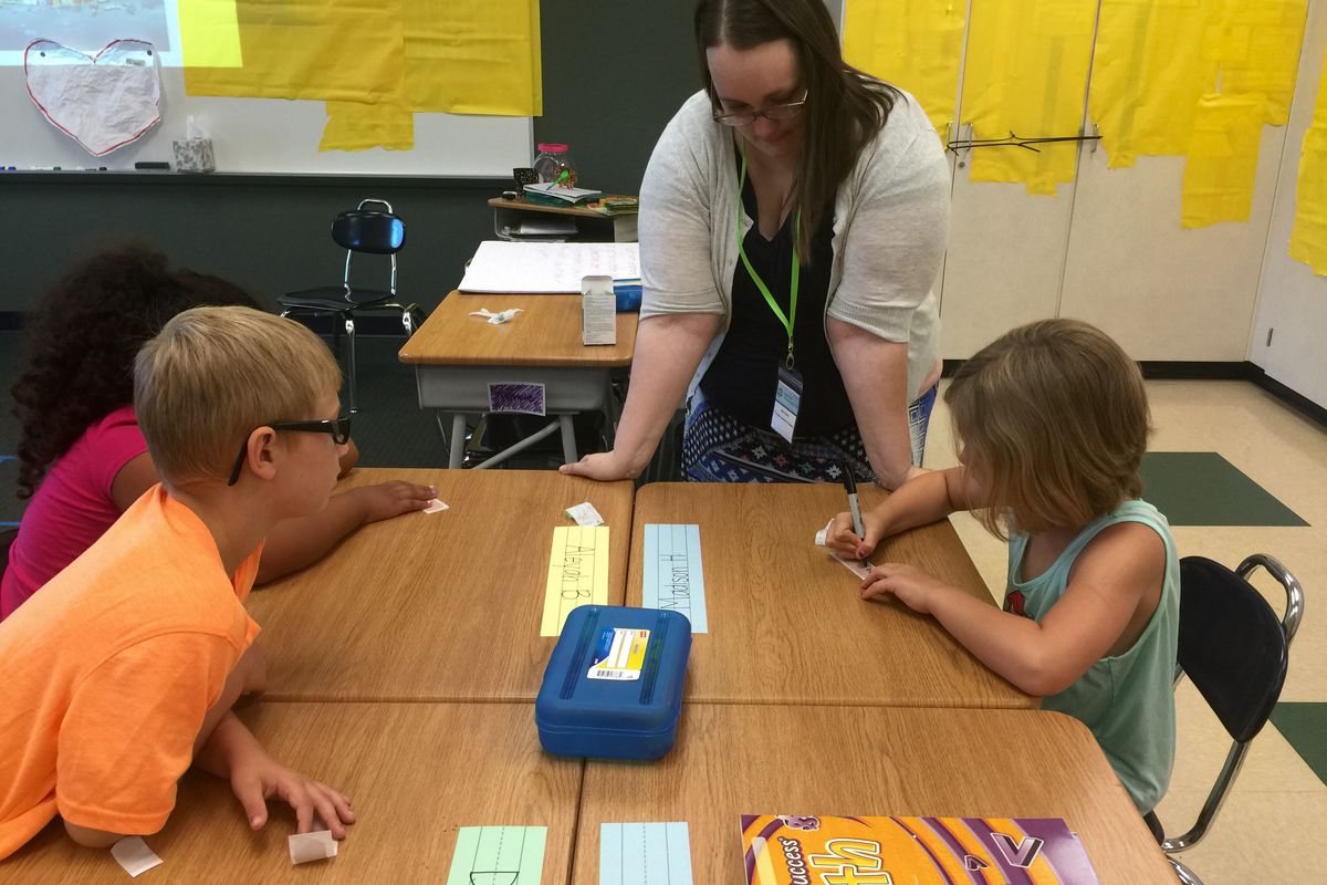 Mave Davis, a first grade teacher for Summer Advantage, looks on as a couple of students practice writing their names June 15 at Stephen Decatur Elementary School. Only 160 kids were able to participate this year, down from last year's 350.