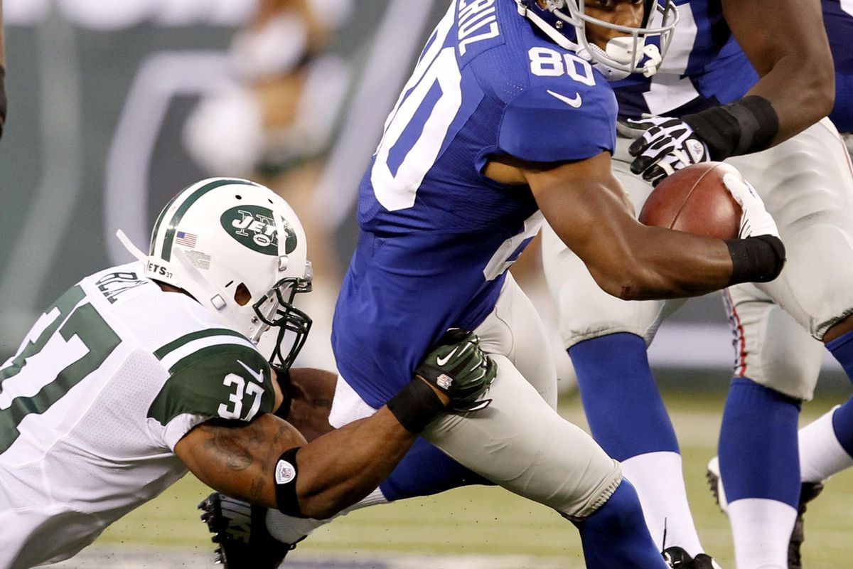 Aug 18, 2012; East Rutherford, NJ, USA; New York Giants wide receiver Victor Cruz (80) is tackled by New York Jets defensive back Yeremiah Bell (37) during the game at MetLife Stadium.  Aristide Economopoulos/THE STAR-LEDGER via US PRESSWIRE