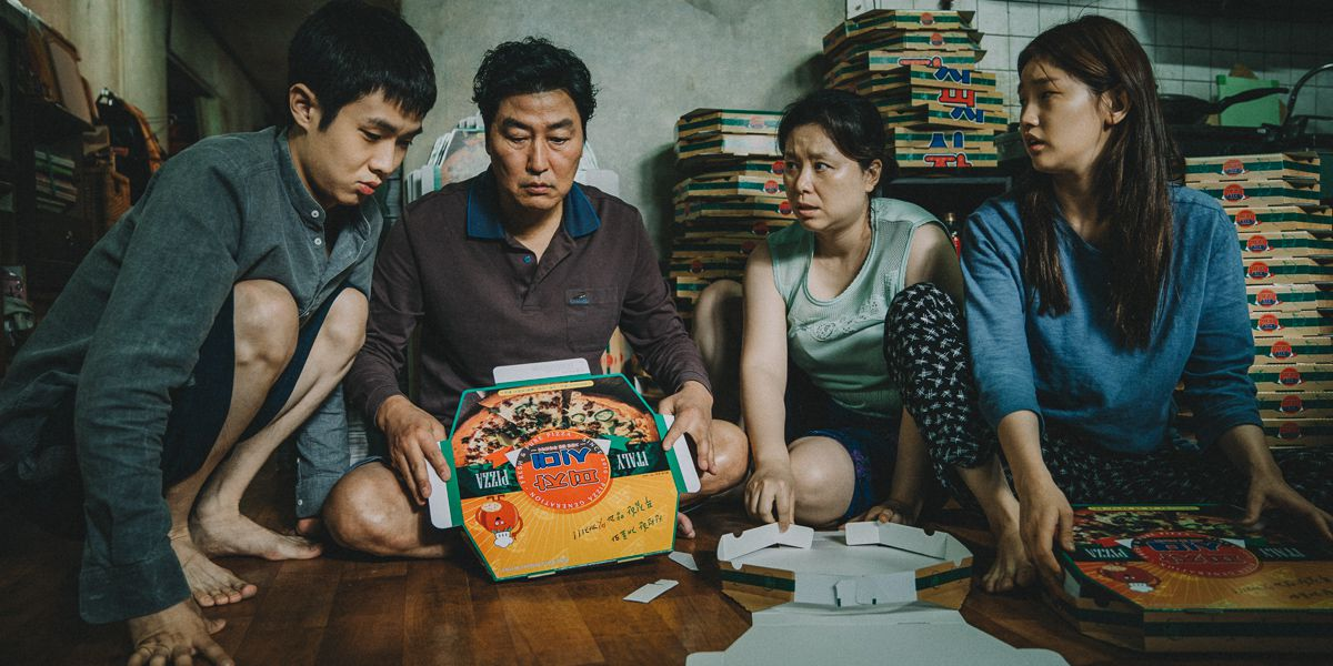 A scene from Parasite, in which a family is folding pizza boxes.