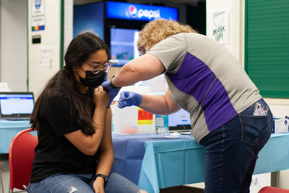 A young girl sitting on a red chair wearing a black shirt with a long, black ponytail holds up her sleeve while a woman in a blue and gray shirt stands next to her and inserts a syringe in her shoulder.