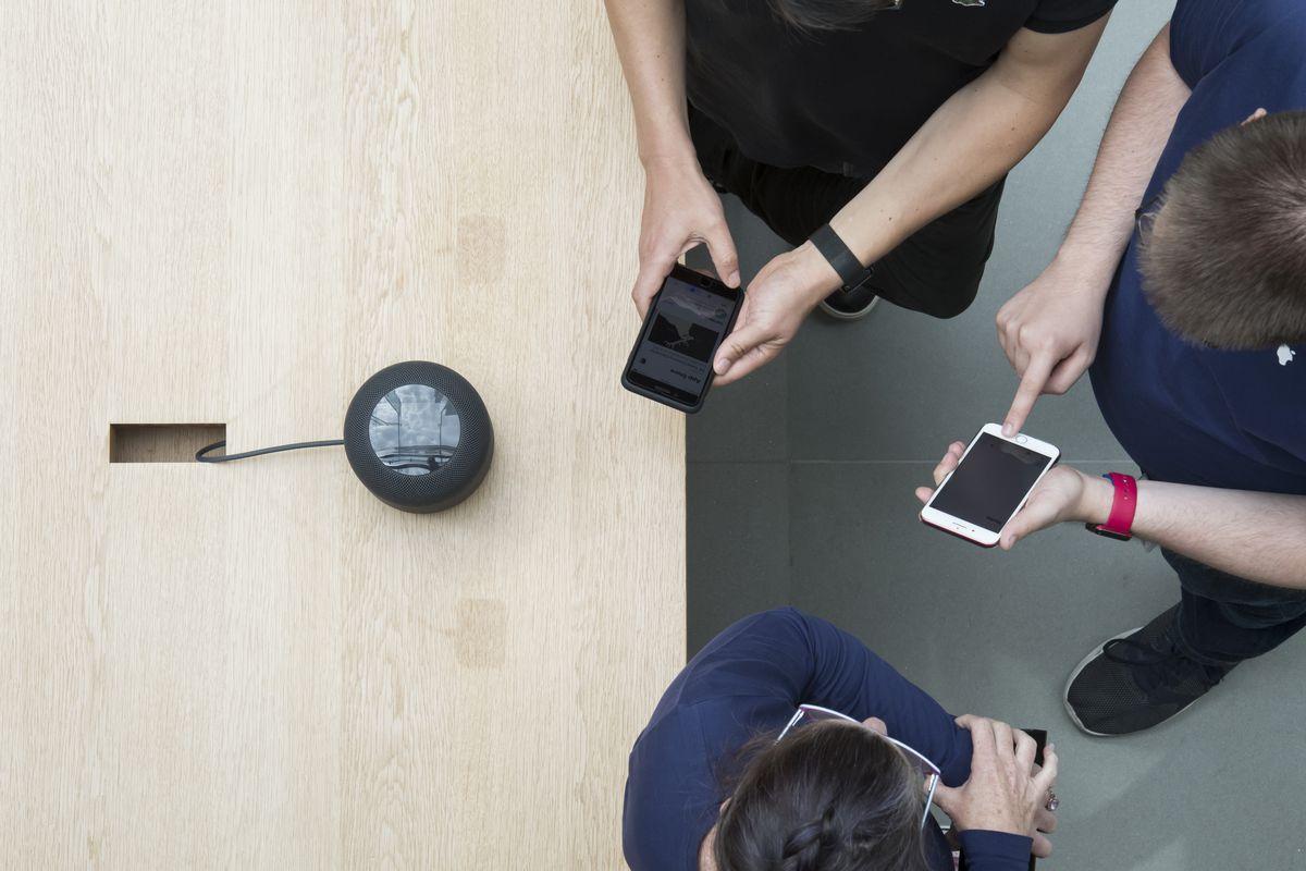 People with smartphones standing around a smart speaker.