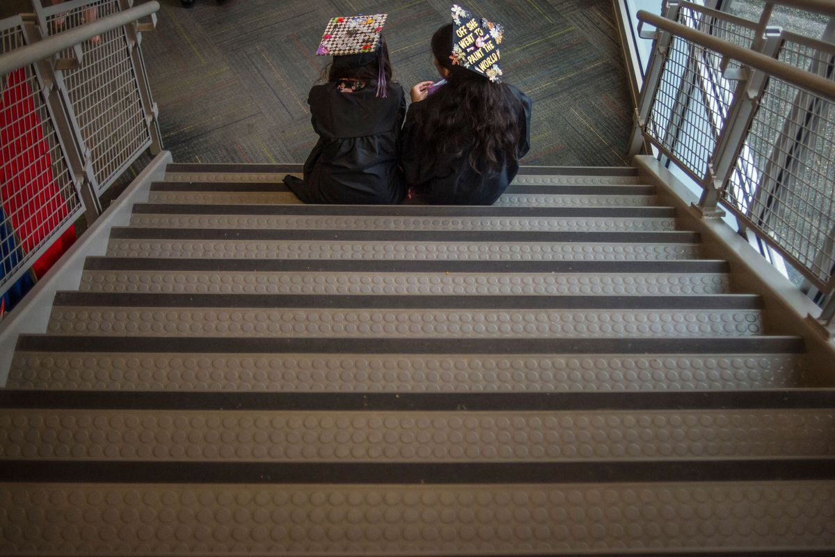 High school graduates in caps and gowns sit on a staircase.