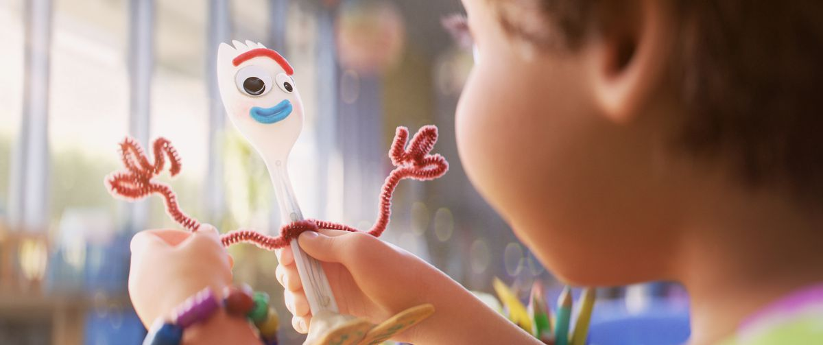 a young girl holds up a handmade toy consisting of a spork with googly eyes, red pipe cleaner arms, and popsicle stick feet