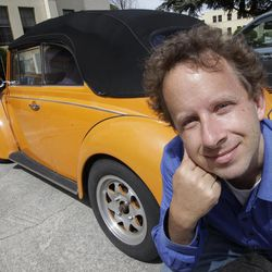 In this April 12, 2012 photo, Kaggle's president and chief scientist Jeremy Howard poses with an orange Volkswagen in Mountain View, Calif. The founders of San Francisco startup Kaggle believe the problems data scientists solve are so important that they should be paid like professional athletes. By turning data science into a crowd-sourced contest, they hope they have created a way to make that happen. Kaggle hopes top contenders will participate in a sport tailor-made for the 21st century: Competitive number-crunching. As part of a study Howard found orange used cars are more likely to be a lemon.