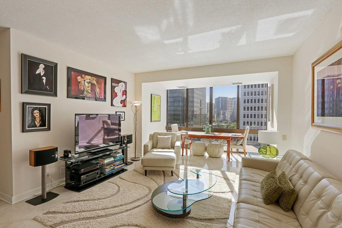 A white condo with a white couch at right and skyline views out the window.