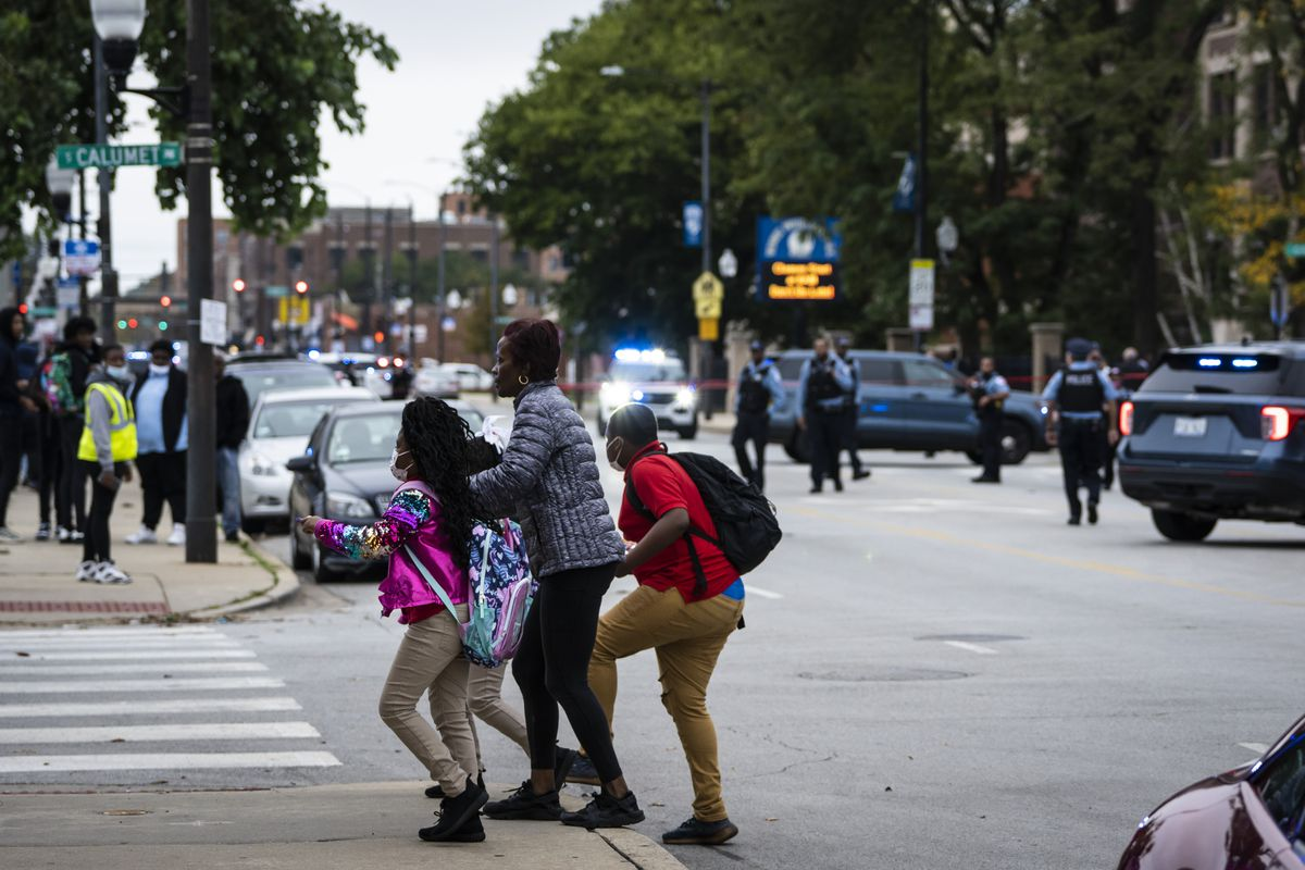 A family walks past the crime scene tape after a 14-year-old girl and a security guard were both shot Tuesday afternoon outside Wendell Phillips Academy High School in the 3800 block of South Giles in Bronzeville.