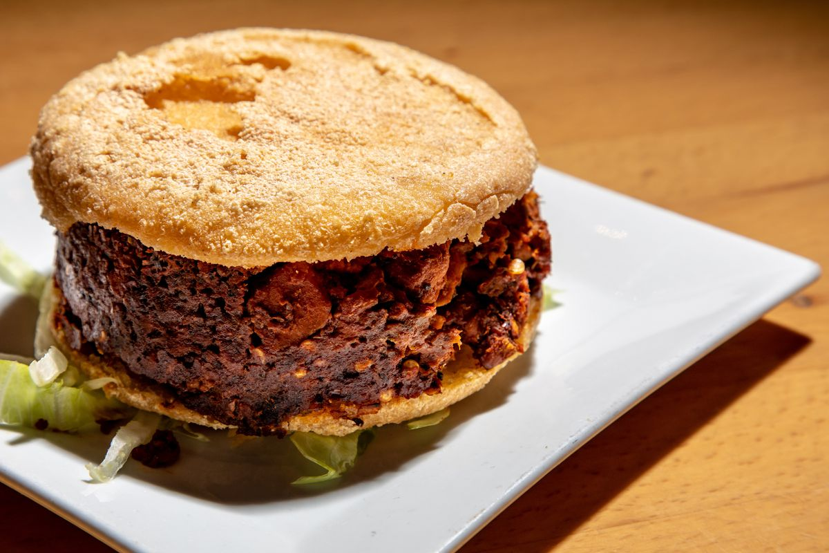 Mahogany chicken sits sandwiches in between two corn arepas
