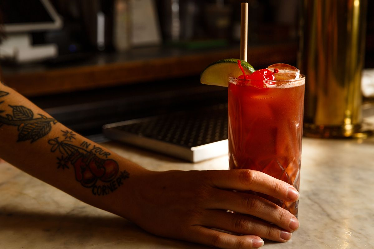 The hand of a staffer with a tattooed arm is shown holding a glass of homemade cherry coke with a metal straw protruding upward