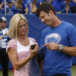 Married opposing fans Jeremy and Kristin Andrus stand on the field prior to the Utah BYU game in Provo on Saturday, Sept. 9, 2017.