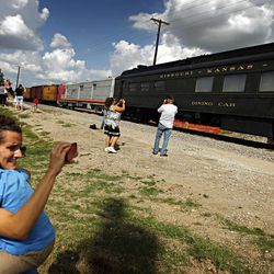Claudia Montanari holds her two-year-old son, Gabriel Montanari, over her shoulder as she snaps photographs of cars from the Museum of the American Railroad arriving pulling in to their new home Monday, Aug. 27, 2012 in Frisco, Texas.  The Museum of the American Railroad is relocating from Fair Park to Frisco in the coming weeks.  The unprecedented move of such a wide array of trains has piqued the interest of railroad buffs around the globe. The one-of-a-kind collection spans the golden era of railroads from 1900 to 1970. Its roster of rolling stock comes from the West Coast, the East Coast and places in between. Each of the 40 pieces carries with it a bit of history.