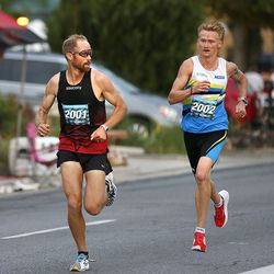 Jared Ward, left, watches as Rory Linkletter catches up to him during the Deseret News 10K in Salt Lake City on Friday, July 23, 2021.