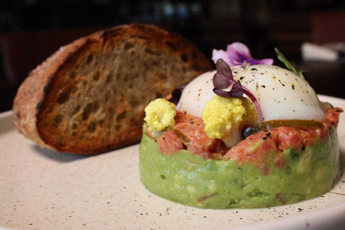 Steak tartare with avocado and a slice of bread.