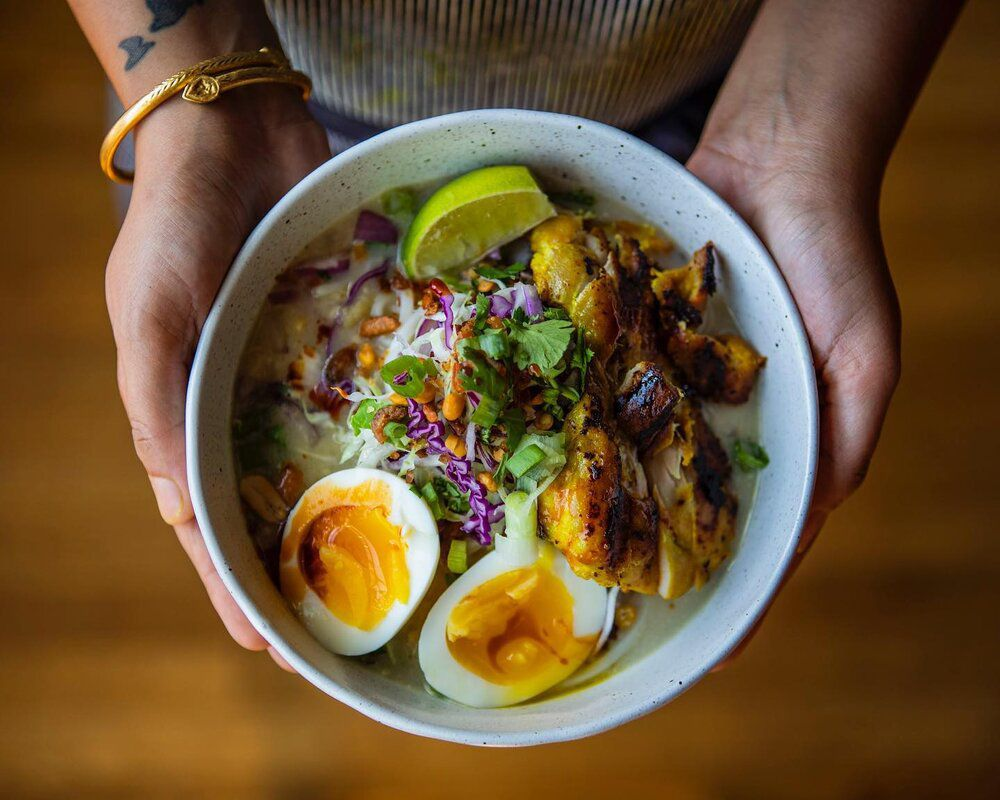 From above, a person holds a bowl of noodles topped with chicken, boiled egg, peanuts, cabbage, cilantro, and lime