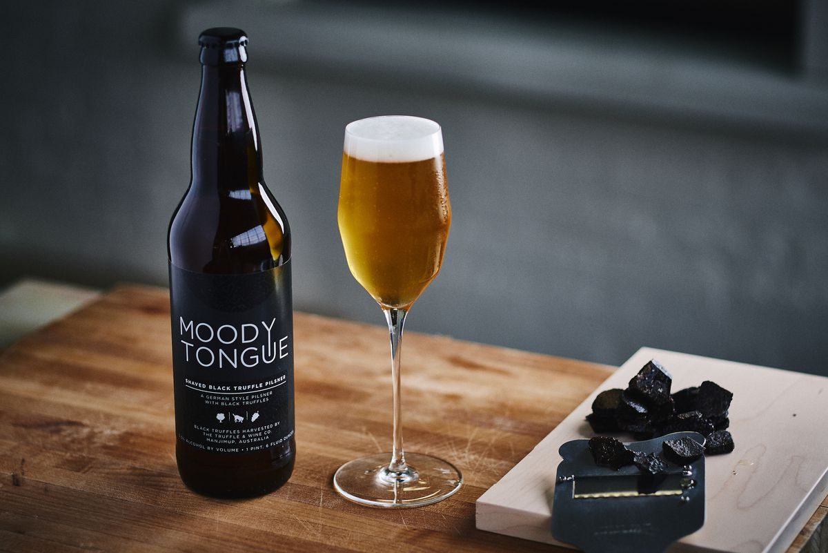 A beer bottle, a tulip glass filled with beer, and black truffles.