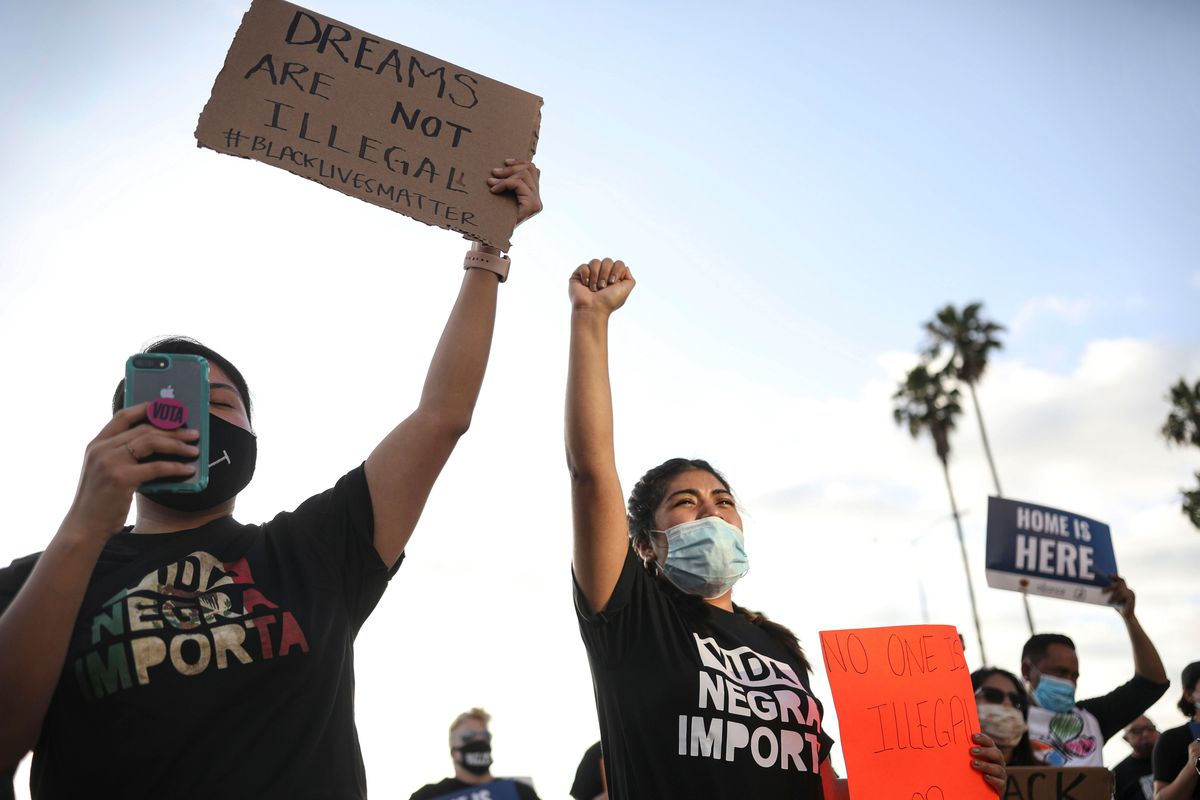 People in San Diego hold signs and a woman raises her fist during a rally in support of the Supreme Court's ruling in favor of the Deferred Action for Childhood Arrivals (DACA) program.