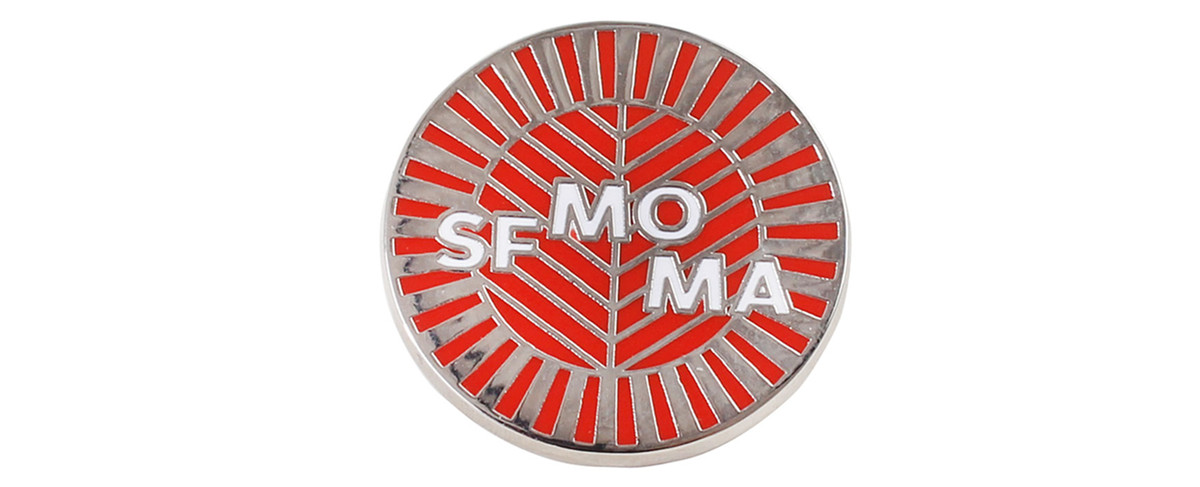 A pin with a red and metallic silver pattern depicting the original facade of the San Francisco Museum of Modern Art. There are white letters on the pin which read: SF MOMA