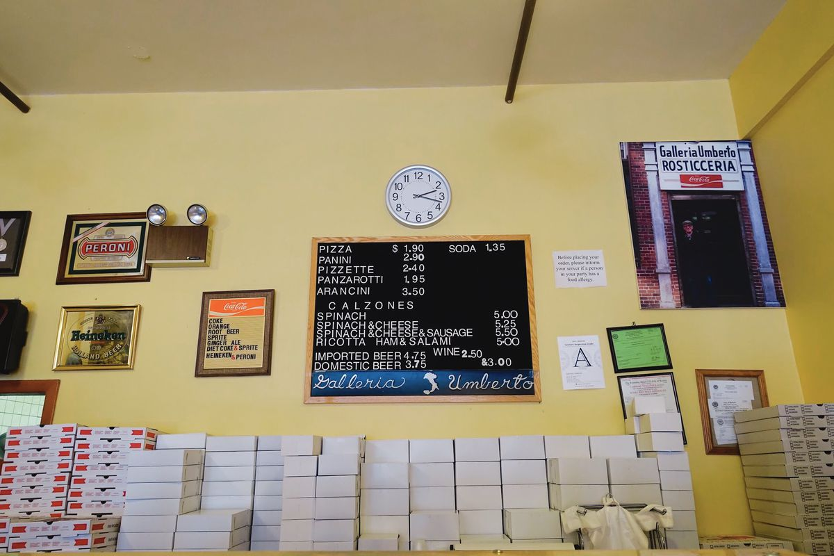 The short menu board — featuring pizza, arancini, calzones, and not much more — and piles of boxes at Galleria Umberto