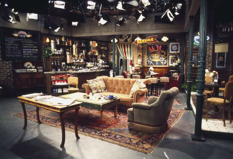 The set for the Central Perk coffee shop, featuring an orange tufted couch, tables, chairs, and the bar at the back.