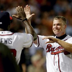 In this photo taken Sept. 25, 2012, Atlanta Braves' Chipper Jones, right, celebrates after the Braves beat the Miami Marlins 4-3 in a baseball game in Atlanta, to clinch a playoff spot. With one last trip to the postseason assured, Jones is relishing the final days of his last season. Jones, who will be honored by the Braves before Friday night's game against the Mets, says he is savoring the final days of his last regular season as he and his teammates look forward to the playoffs.