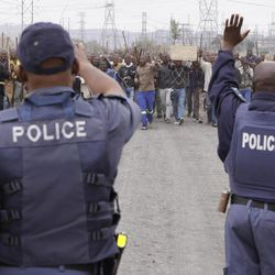 Police try to prevent striking mine workers marching to the Karee  shaft at the Lonmin Platinum Mine near Rustenburg, South Africa Wednesday, Sept, 5, 2012 to hand over a memorandum to mine management. Miners are refusing to return to work  until their demands  over low pay and working conditions are met. Three weeks ago 34 miners were shot and killed by police.