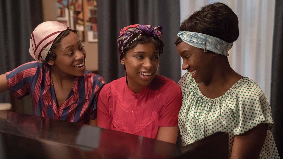 Three women sit at a piano, singing.