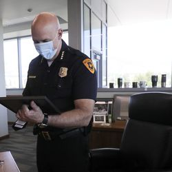 Salt Lake Police Chief Mike Brown looks at a photo of his father getting sworn in as a police officer during an interview in his office in Salt Lake City on Wednesday, July 15, 2020. Brown's father died on June 4th, during one of the busiest and most challenging months the Salt Lake City police department has faced.